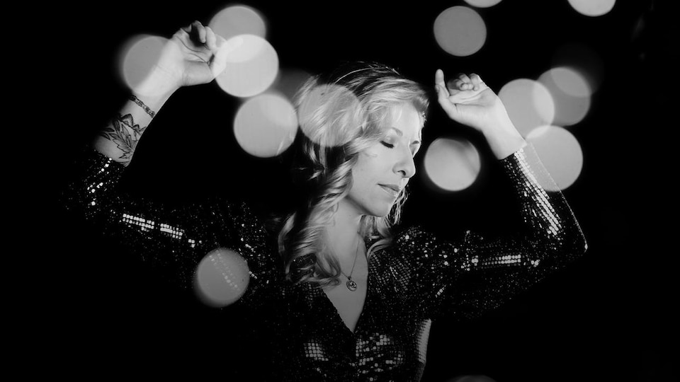 Photo noir et blanc : Cindy Bédard en robe de soirée, un casque d'écoute sur les oreilles, les yeux fermés et les deux mains levées au niveau de sa tête, comme si elle dansait.