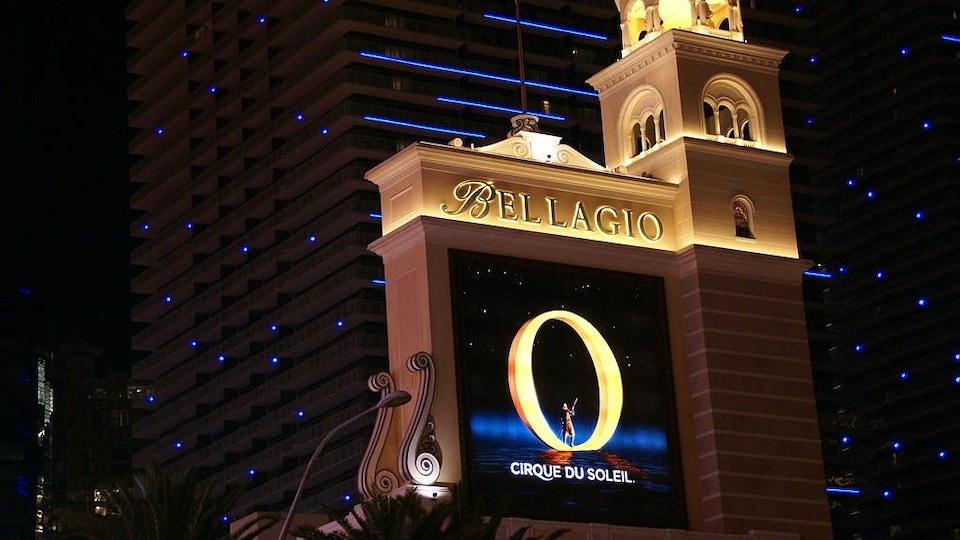 On voit l'affiche du spectacle, illuminée, sur la devanture d'un hôtel de Las Vegas.