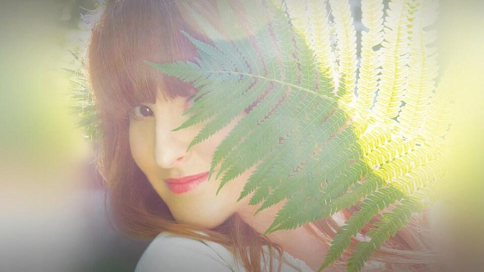 La chanteuse Diana Panton cachée derrière une fougère.