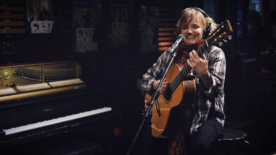 Diane Tell interprète à la guitare une chanson en studio à Tellement Courteau.