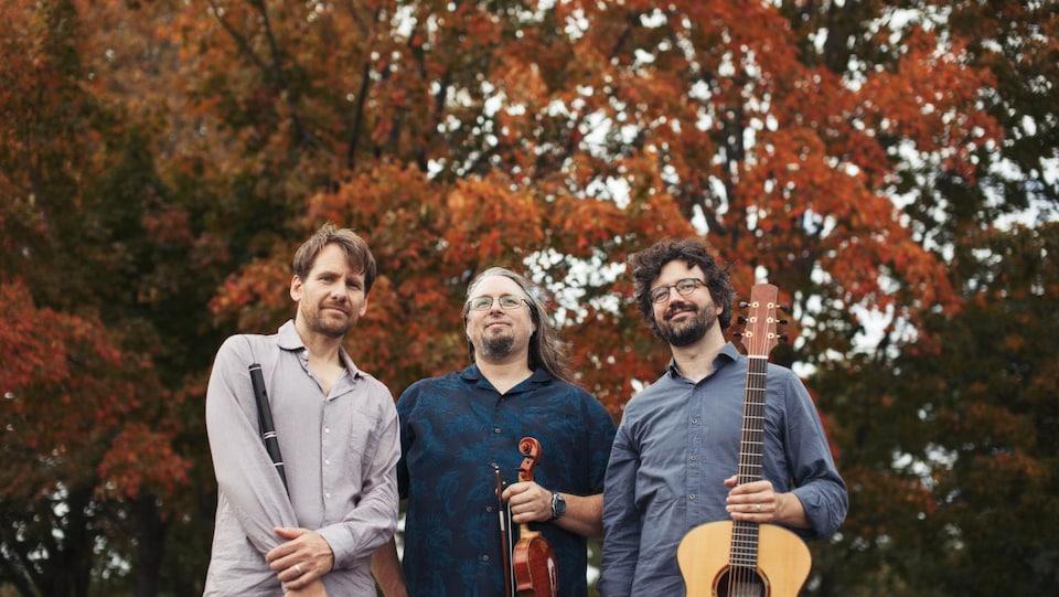 Les trois membres du groupe tenant des instruments photographiés devant un arbre en couleurs
