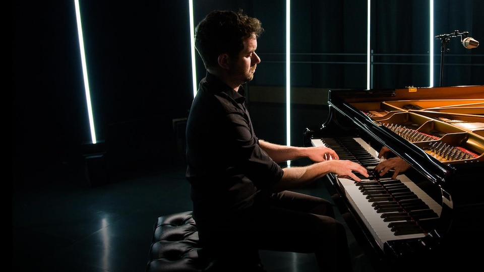 Le pianiste pose les doigts sur les touches de son piano.