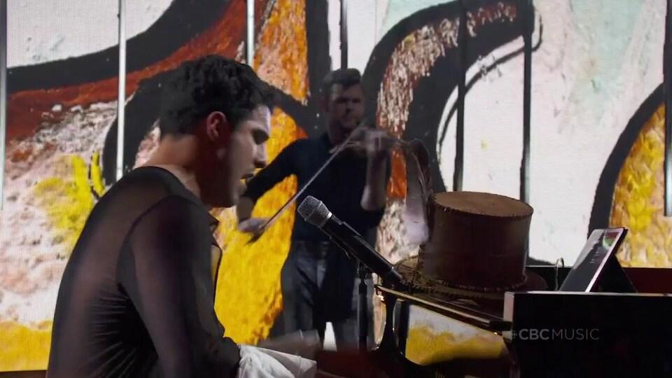 Intérieur. Le musicien chante, assis au piano à queue. Un violoniste joue derrière lui.