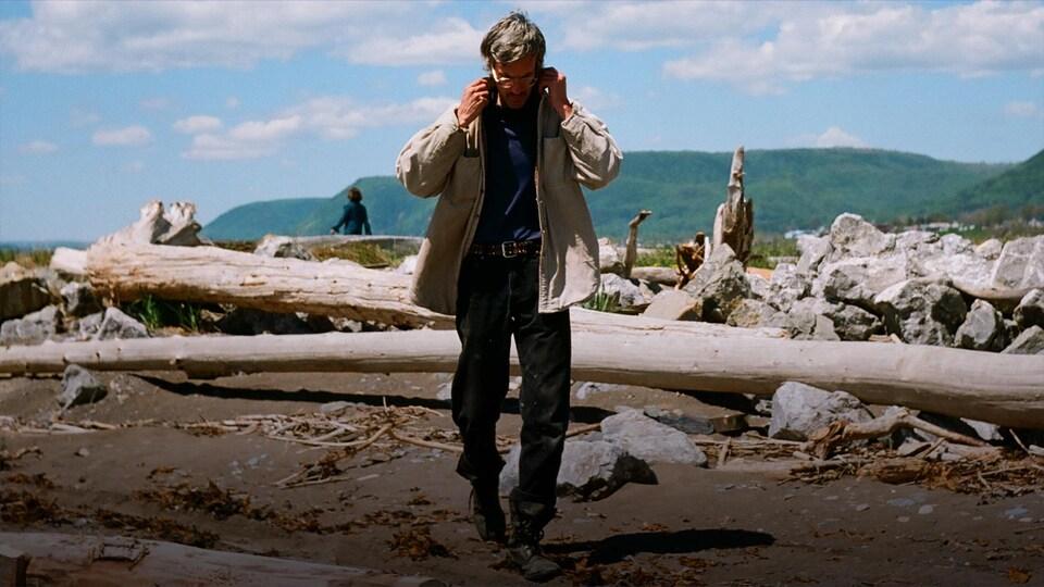 Le chanteur marche dans un paysage de la Gaspésie en remontant le collet de son manteau.