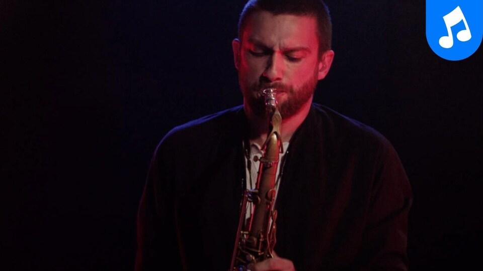 L'artiste joue du saxophone sur une scène à l'éclairage tamisé.