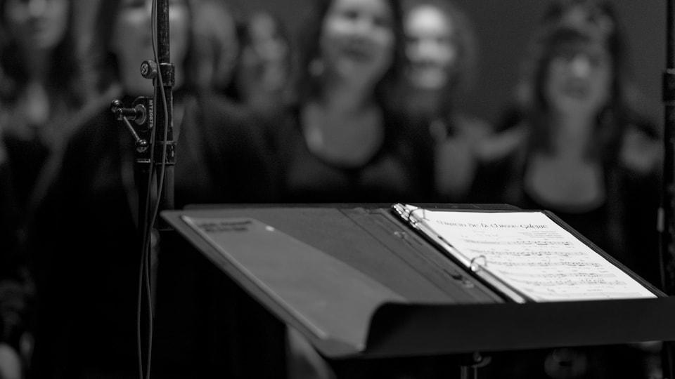 Un lutrin, une partition et une chorale en arrière-plan.