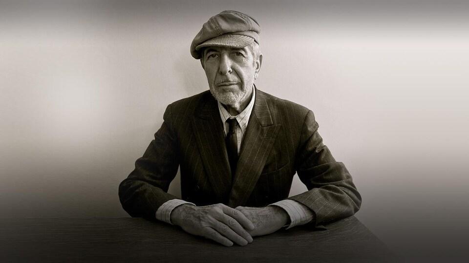 L'artiste est assis à une table, les mains croisées, le regard qui pointe vers la caméra.
