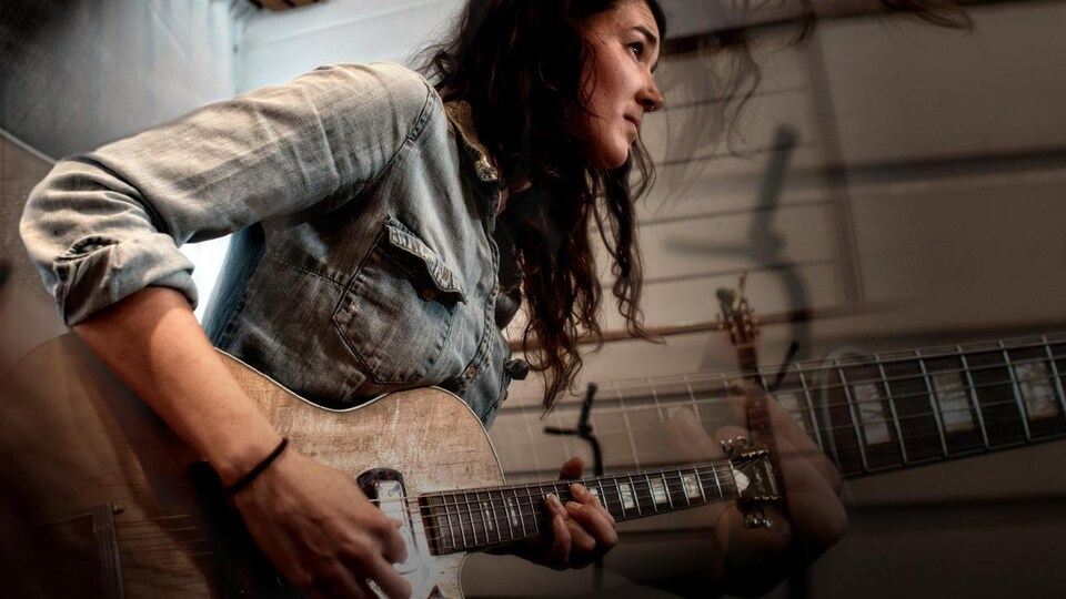 Maggie Savoie à la guitare dans ce qui semble être un studio. Elle est de profile et porte une chemise en jeans.