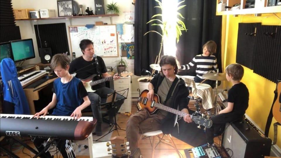 L'auteur-compositeur-interprète Manuel Gasse, chez lui, en train de faire de la musique avec ses garçons.