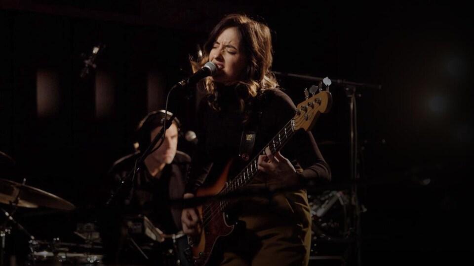 La chanteuse en prestation, les yeux fermés, sa basse dans les mains.
