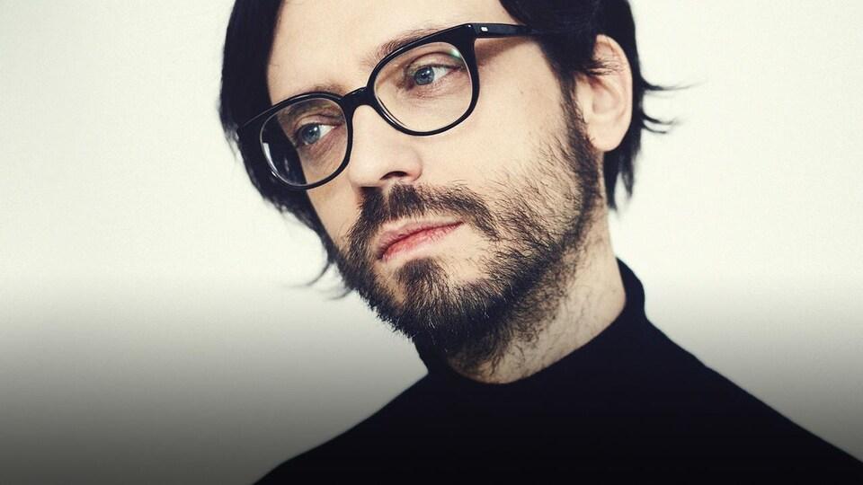 L'homme porte un col roulé noir, une barbe et des lunettes noires.