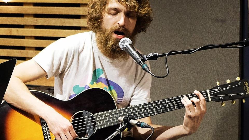 Philippe Brach assis en studio et chantant en s'accompagnant à la guitare