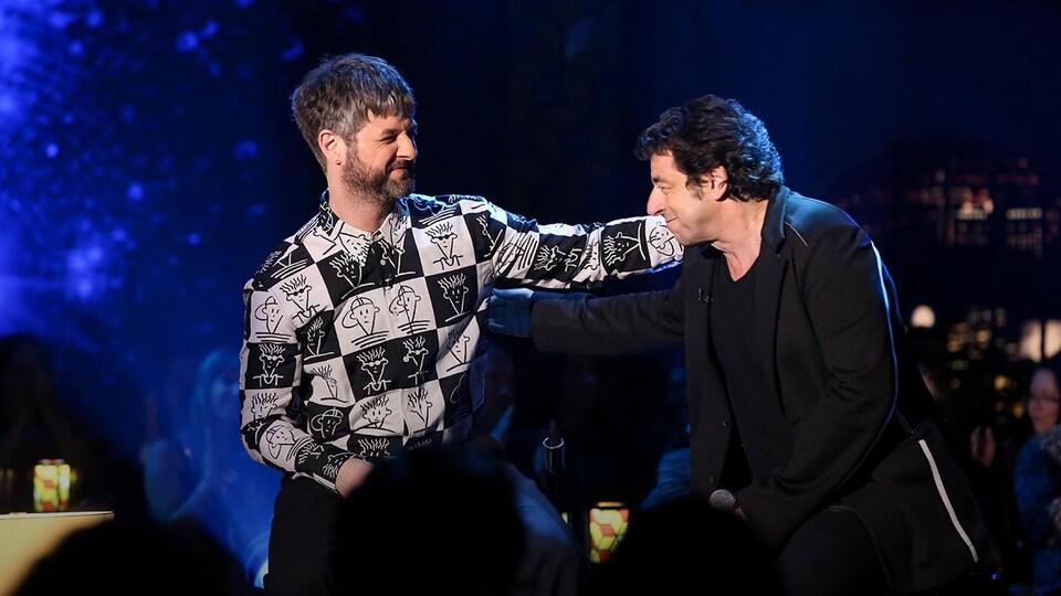 Les deux chanteurs sur le plateau de Bonsoir bonsoir. Pierre Lapointe met sa main sur l'épaule de Patrick Bruel.