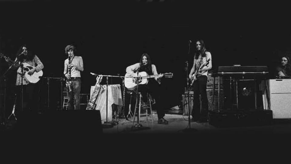 Cinq musiciens d'Harmonium, avec leurs instruments entre les mains, sur une scène.
