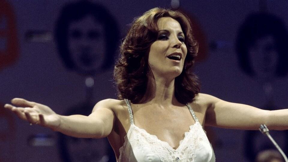 Renée Claude, vêtue d'une robe blanche qui chante devant un micro.