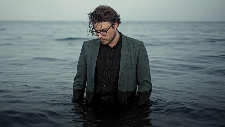 Simon Daniel portant un veston et une chemise, dans l'eau jusqu'à la taille