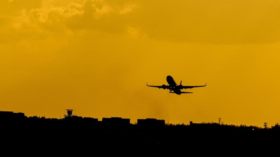 Coucher de soleil. Dans un ciel rendu jaune par le coucher du soleil, on distingue la silhouette d'un avion qui décolle.