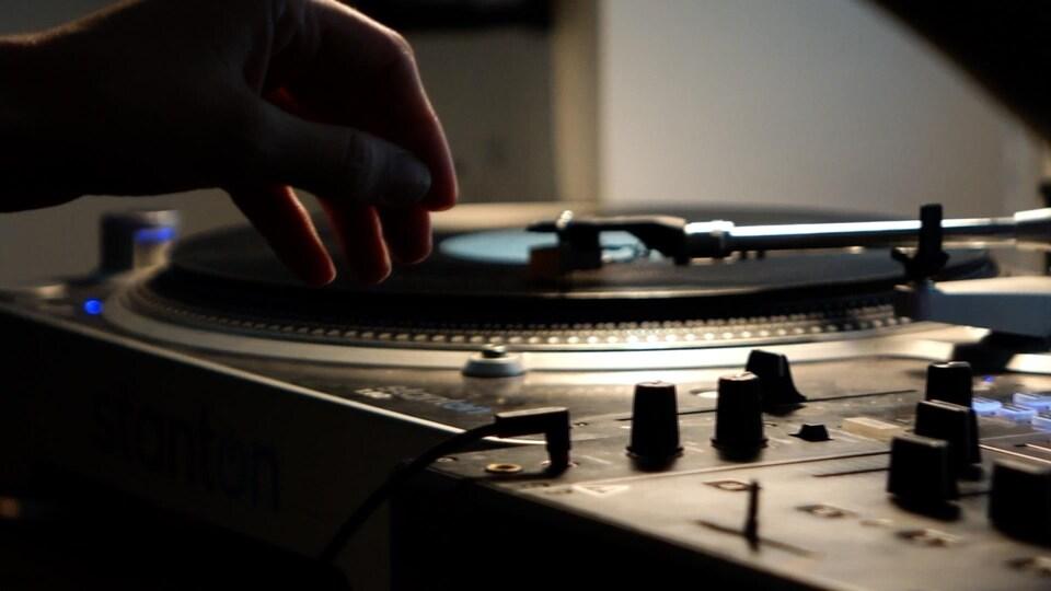 Une main au-dessus d'une plaque tournante de vinyle.