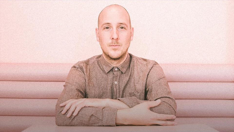 Le musicien Alex McMahon est attablé, assis sur une banquette rose, et regarde en face, les bras croisés. Il porte une chemise beige et a les cheveux rasés.