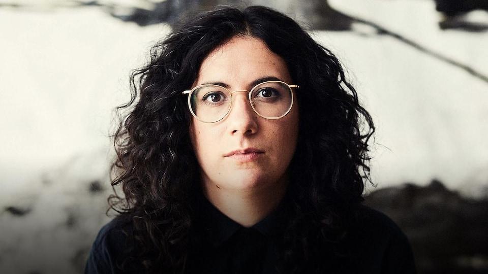Alexandra Stréliski portant des lunettes et regardant directement la caméra, vêtue d'une chemise noire
