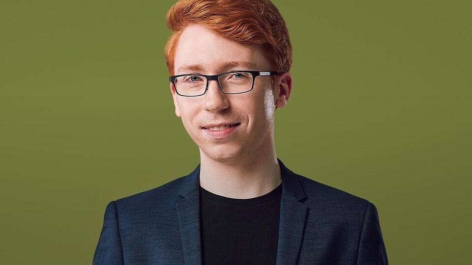 Cameron Crozman portant un veston et un chandail noir devant un arriere plan vert olive