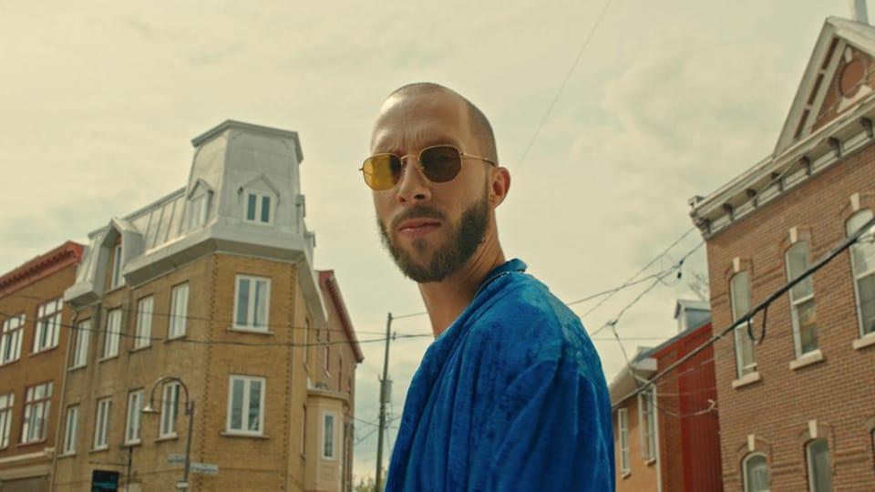 Le rappeur Eman pose dans une rue avec ses lunettes de soleil.