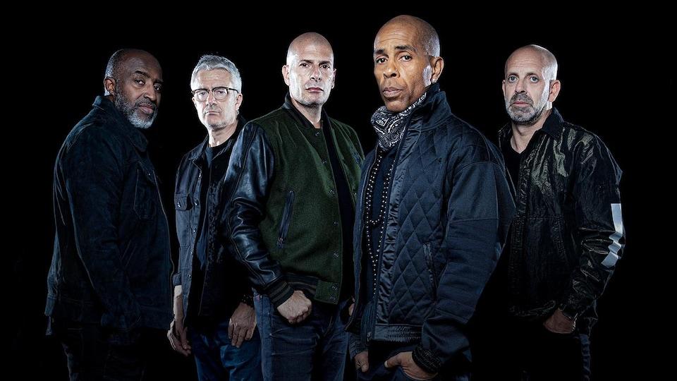 Cinq hommes vêtus de noir posent.