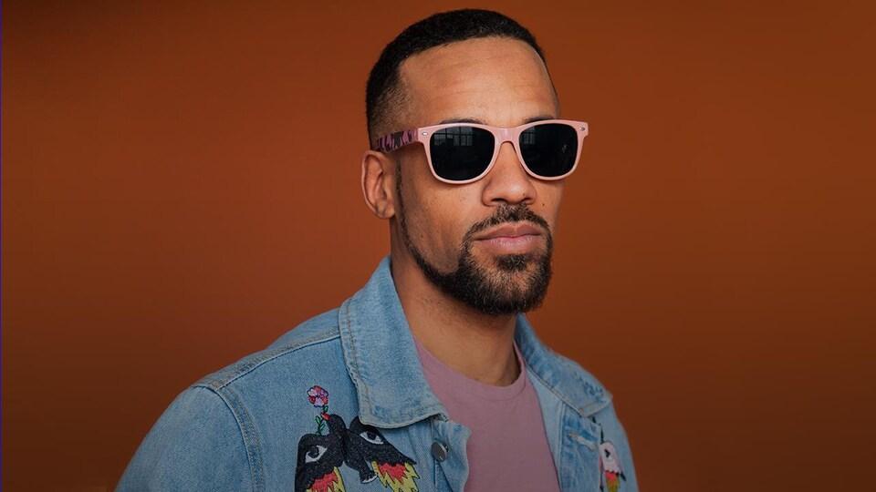 Le rappeur KNLO pose avec ses lunettes fumées.