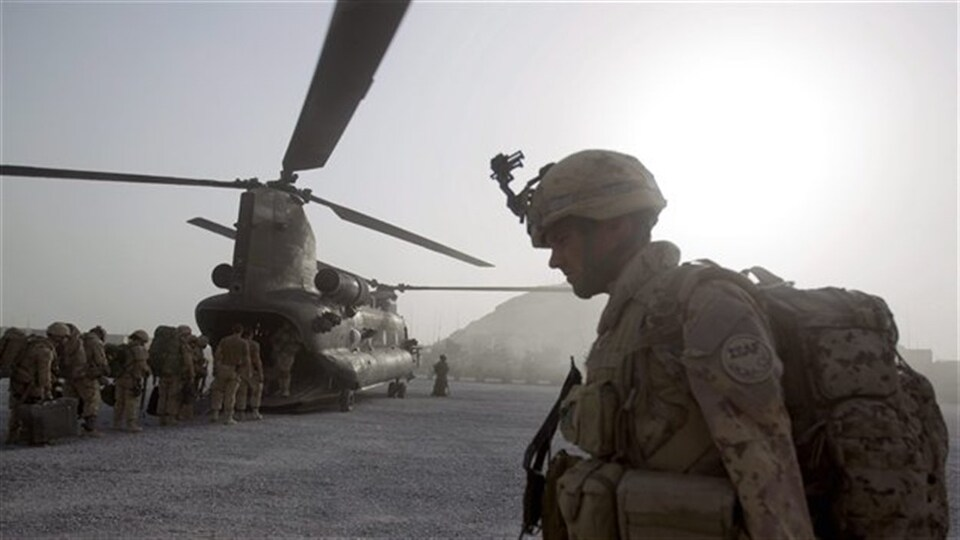 Un soldat marche vers un hélicoptère en Afghanistan.