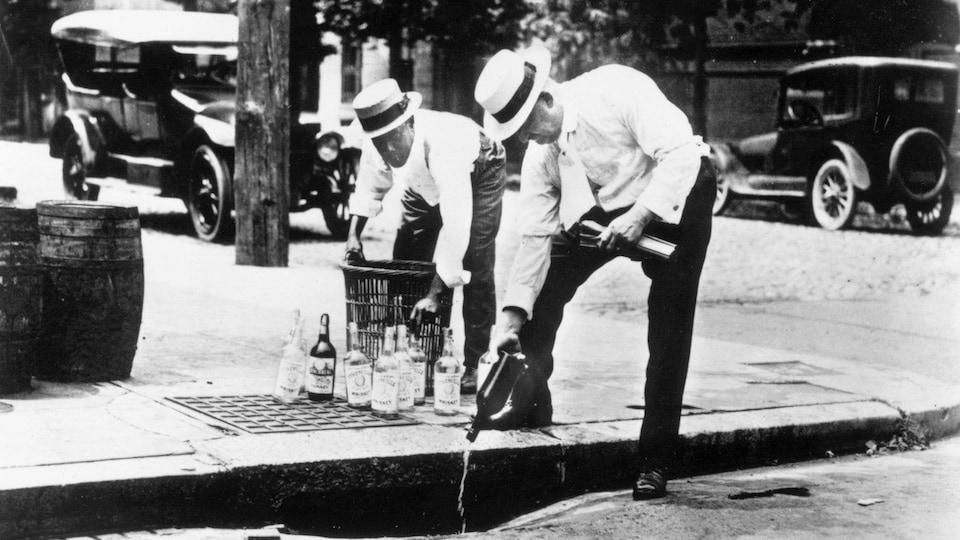 Vers 1920 aux États-Unis, deux hommes versent de l'alcool dans un égout.