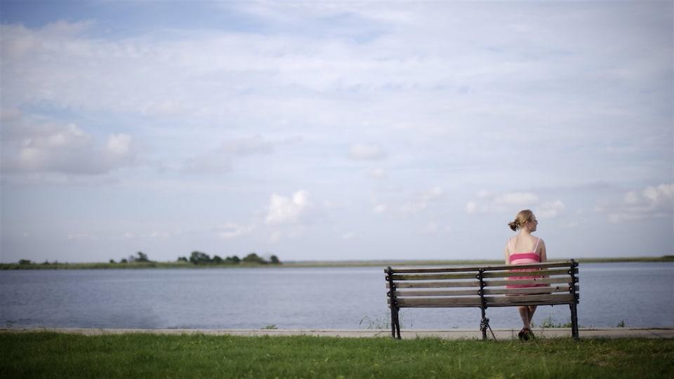 Une femme seule, assise sur un banc, observe l'horizon.