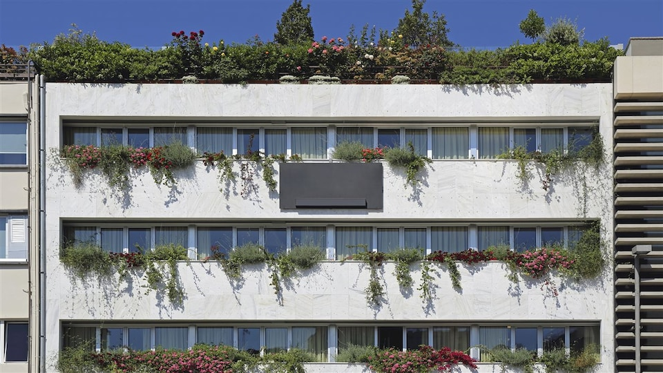 Immeuble dont le toit et les balcons sont recouverts de plantes.