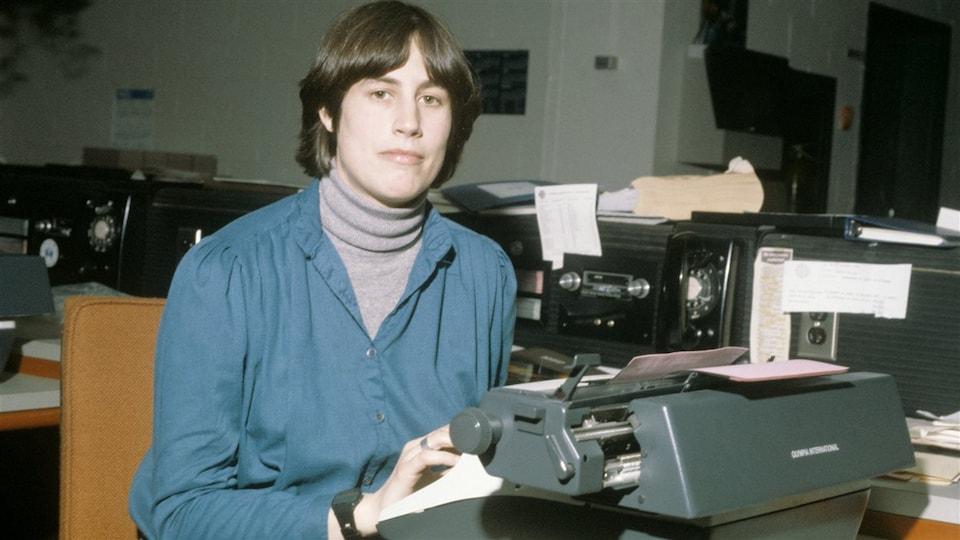 La journaliste Chantal Hébert est assise devant une machine à écrire.
