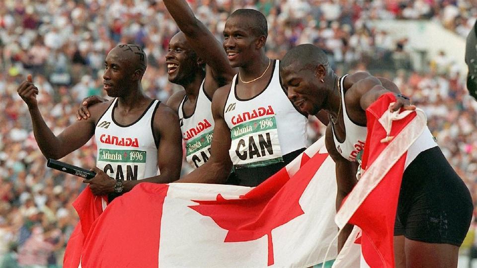 Ils tiennent le drapeau canadien et sourient.