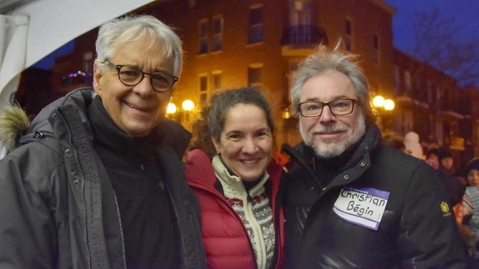 Les trois collaborateurs posent souriants, face caméra, à la lumière de semi-pénombre du petit matin.