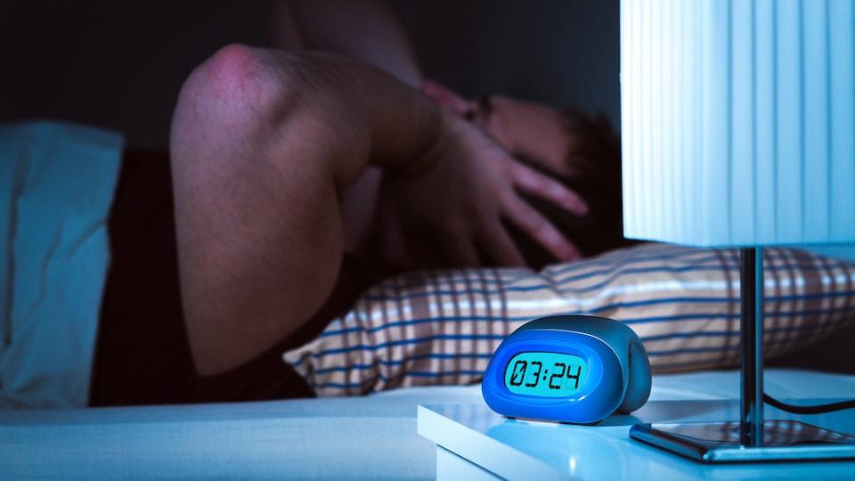 Un homme couvre ses oreilles alors qu'il essaie de dormir.