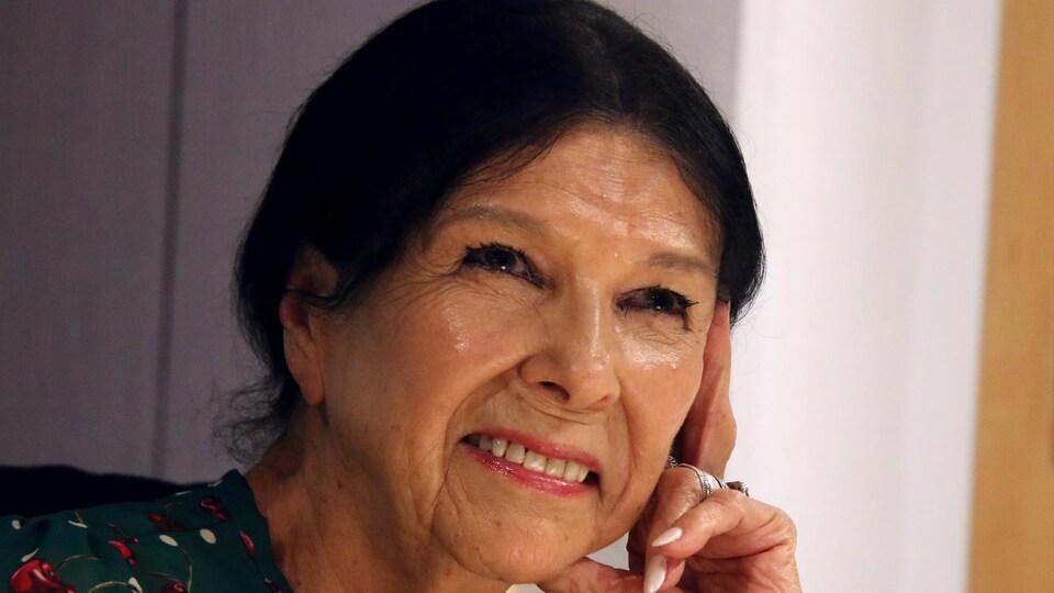 Une femme d'origine autochtone, souriant dans un studio de radio.