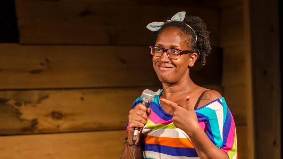 Daphney Joseph sur un scène pour un spectacle d'humour. Elle pointe du doigt le microphone qu'elle tient dans l'autre main.