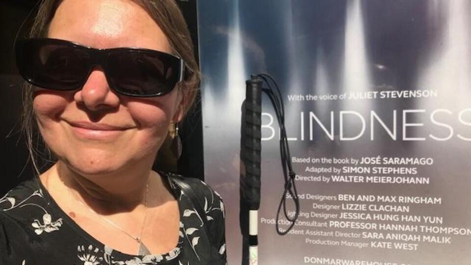 Hannah Thompson posée devant l'affiche de BLINDNESS, qui énumère les membres de la distribution et de l'équipe de production, y compris la photographiée. Elle est souriante, lunettes fumées aux yeux et canne blanche à la main.