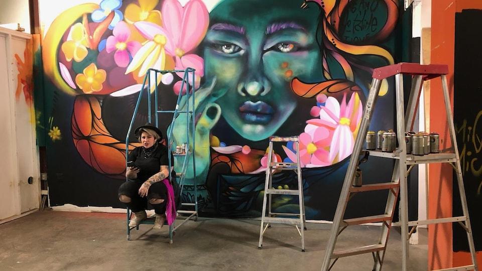 Mique Michelle est assise sur un escabeau devant une murale qui dépeint une femme entourée de fleurs et de couleurs. En avant-plan : des cannettes de peinture à aérosol et d'autres escabeaux.