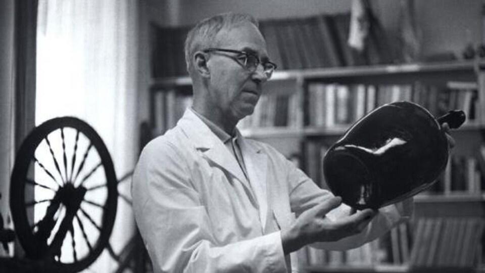 Photo d'archive. Le père Germain Lemieux observe un vase qu'iltient entre ses mains.