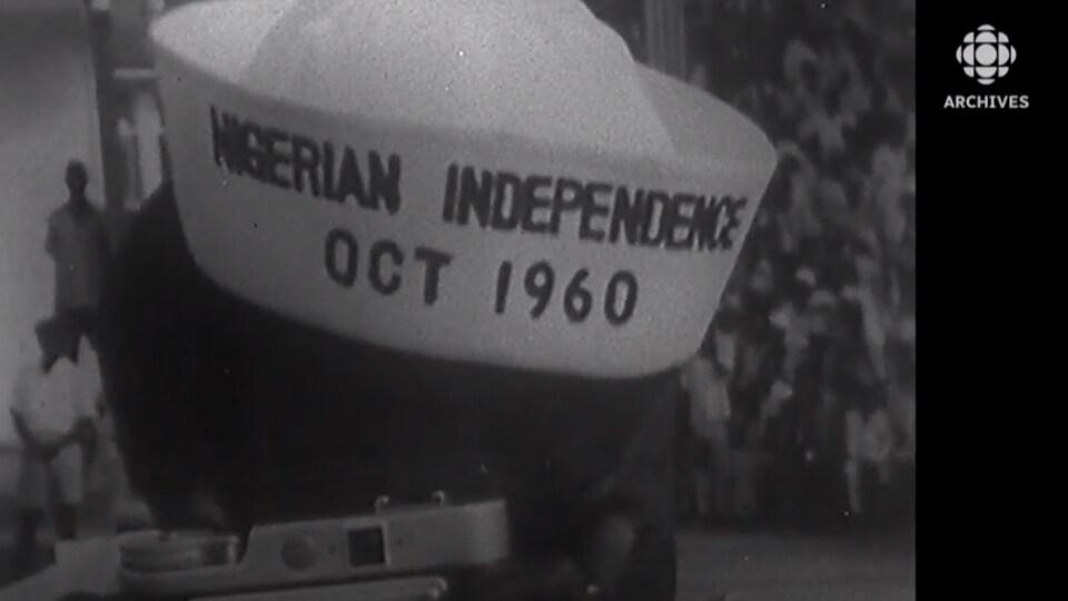 Un homme avec un appareil photo porte un chapeau avec les mots indépendance du Nigeria octobre 1960 écrits dessus en anglais.