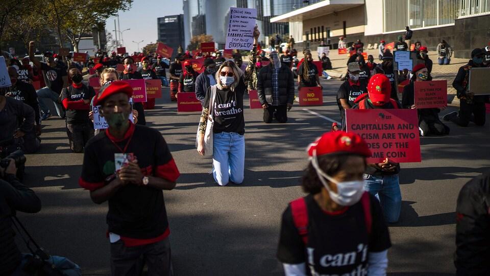 Des manifestants masqués agenouillés dans une rue.