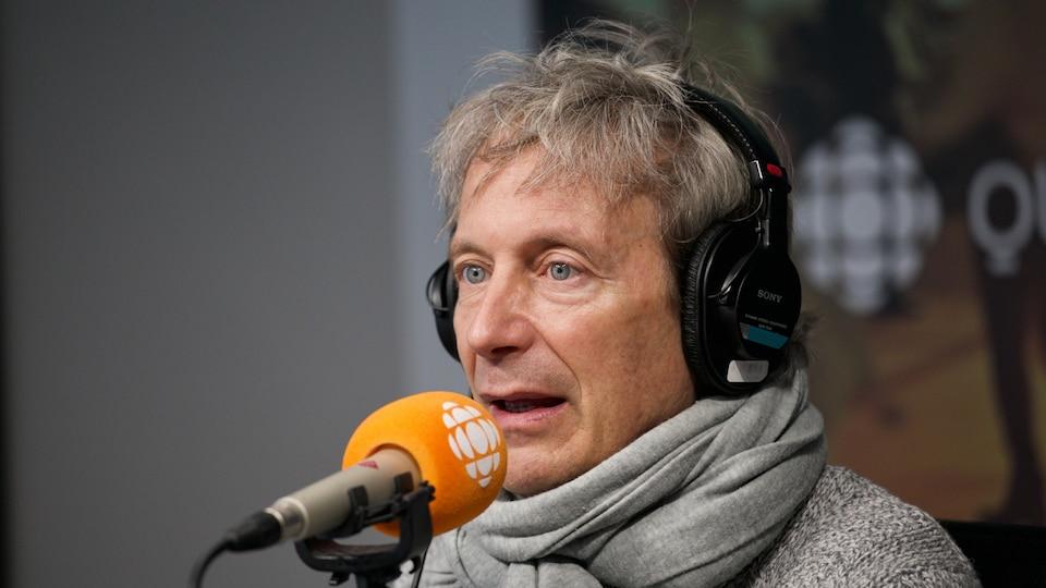 Alain Choquette, un foulard au cou, derrière un micro.