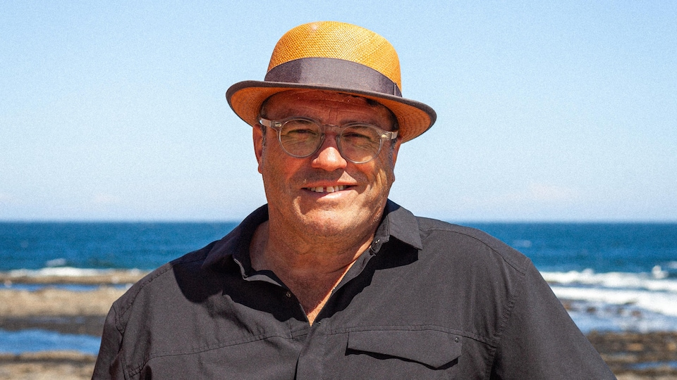 Alan Cote souriant sur la plage