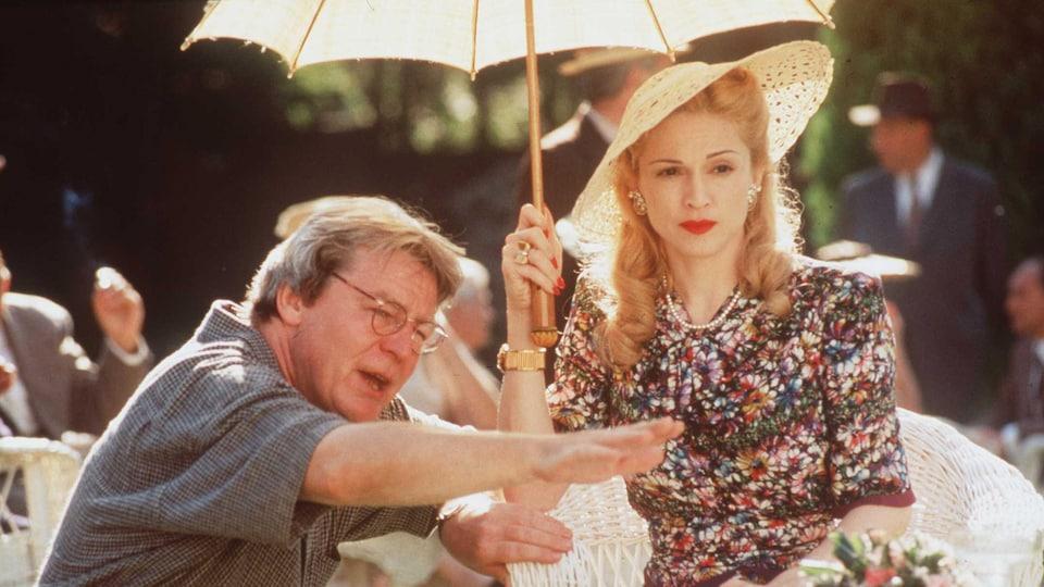 Sur un plateau de tournage, Madonna reçoit les instructions du réalisateur Alan Parker.