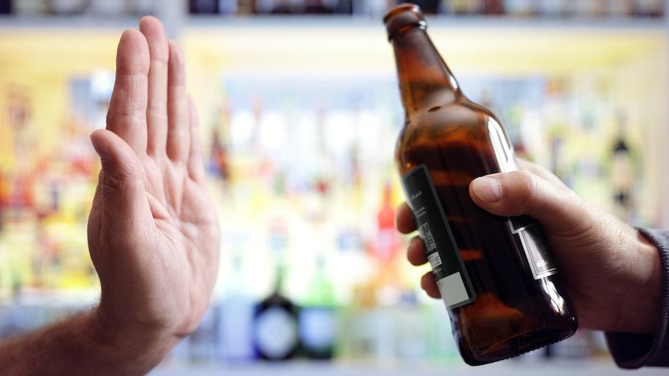 Une main refuse une bouteille de bière.