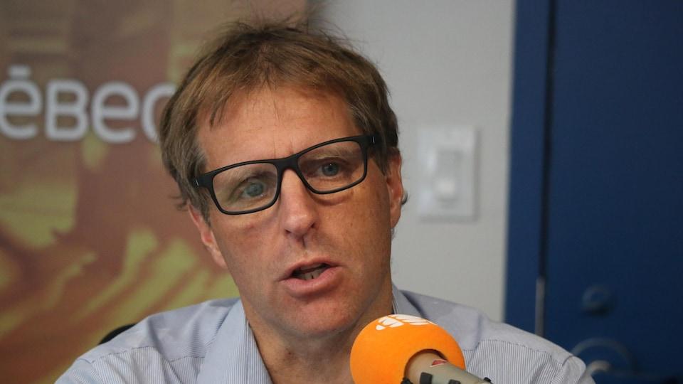 Un homme en chemise à fines rayures blanches et bleues et portant des lunettes de vue à cadre noir parle au micro.