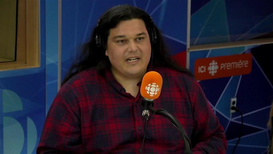 Alexis Wawanoloath derrière un micro dans un studio radio de Radio-Canada.