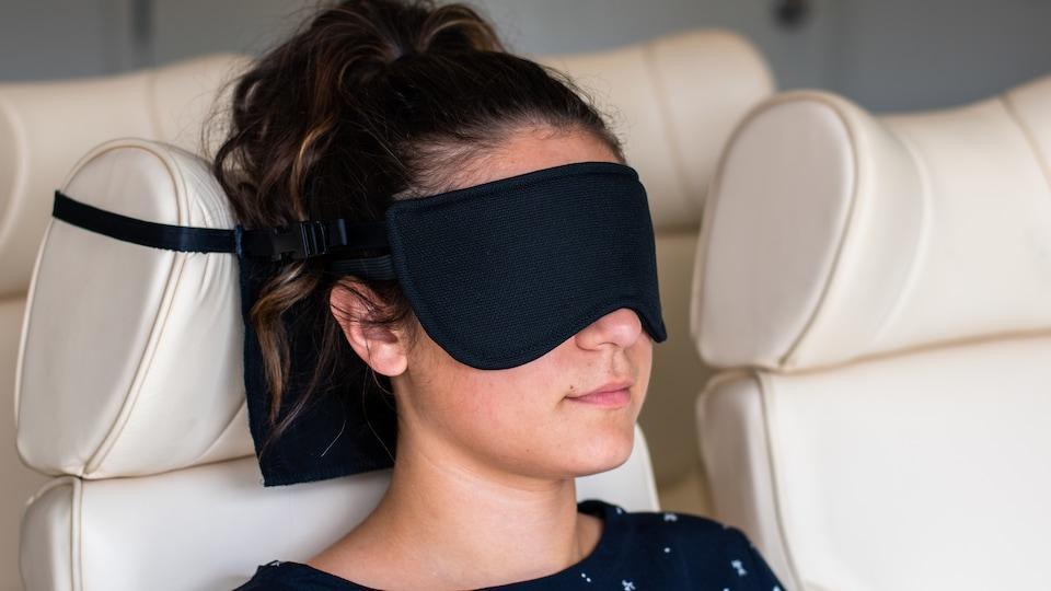 Une femme qui porte un masque pour dormir dans un avion